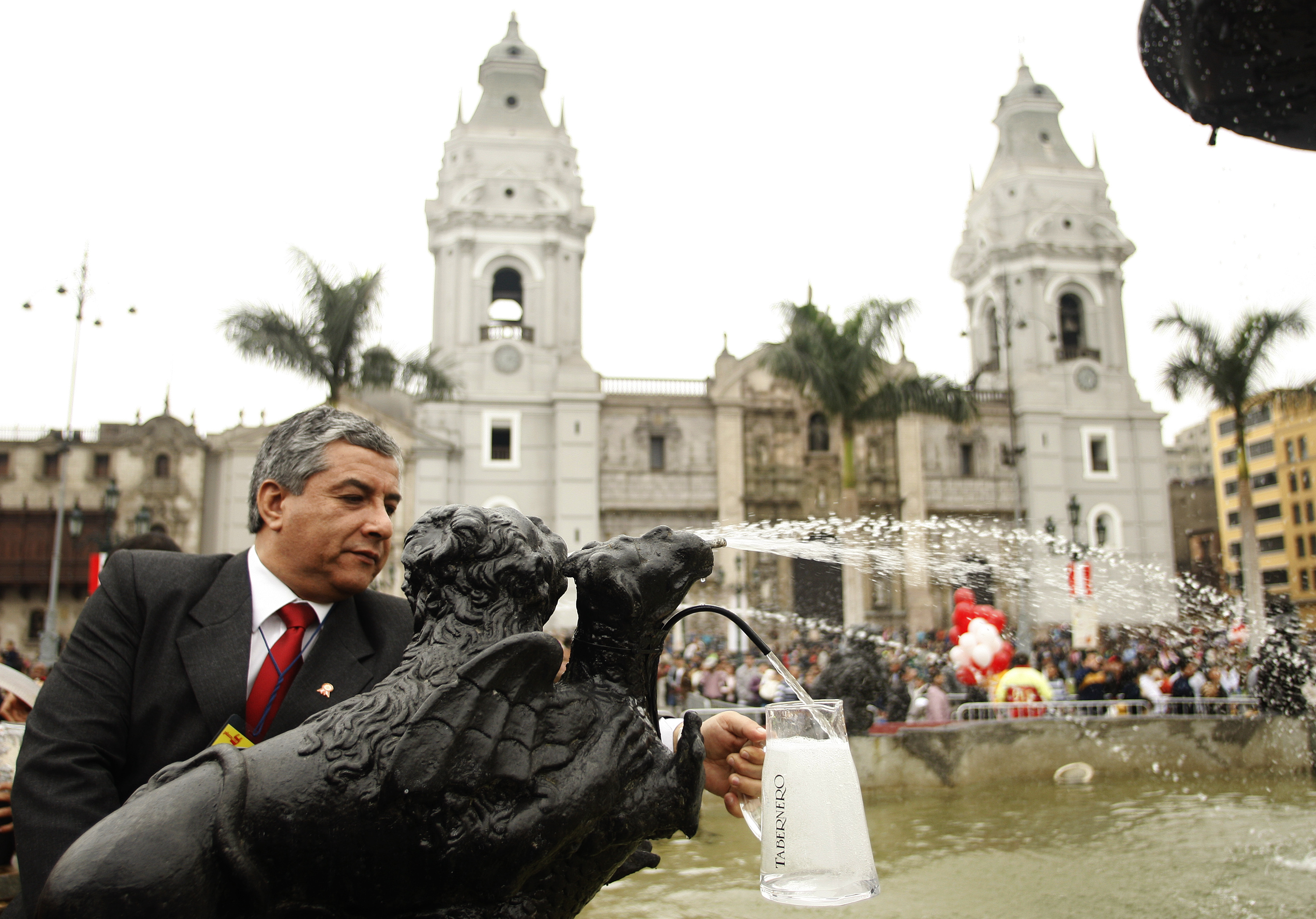 "A man fills a jug with Peru's traditional drink ""Pisco"" from a tap in a fountain in Lima"