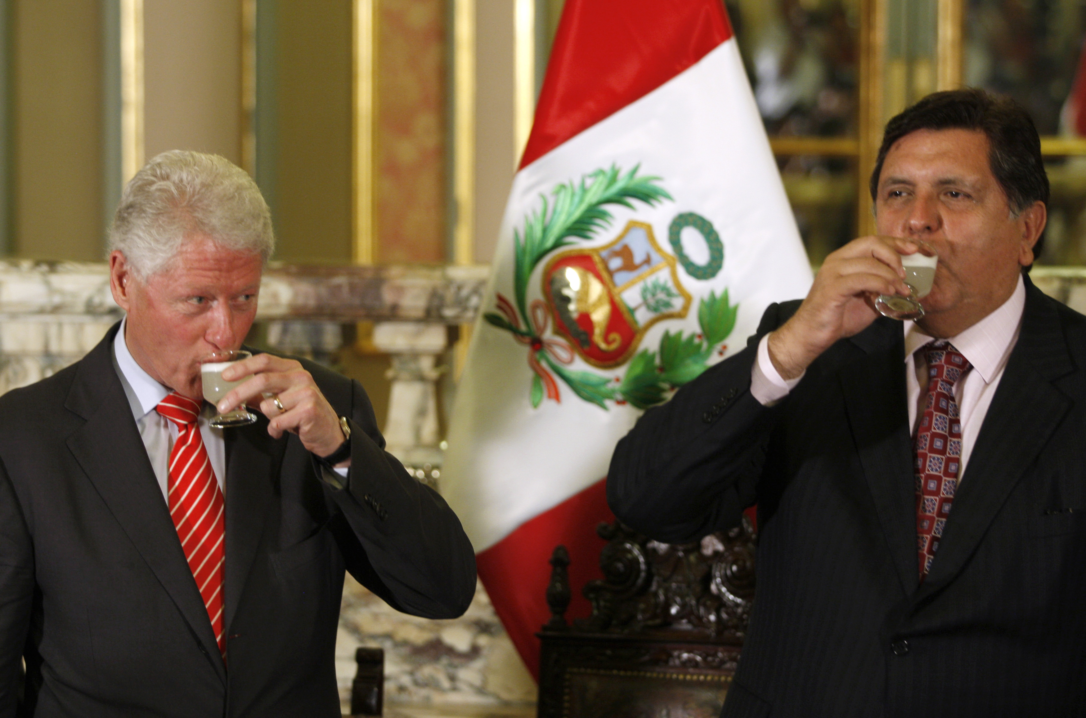 Peru's President Garcia and former US President Clinton drink Pisco Sour after a meeting at the government palace in Lima